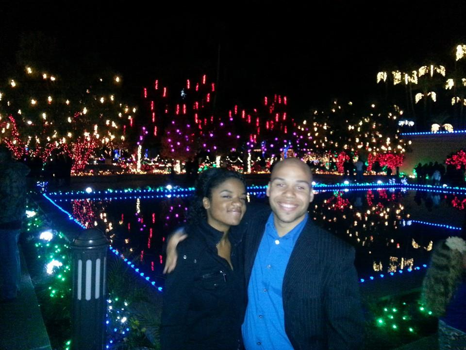 In front of a romantic array of Christmas lights, John Smoot and Brittany Miller celebrate their engagement!