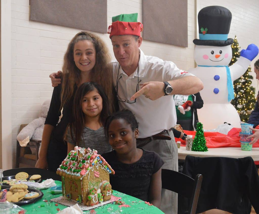 Doug Hunt shares a special moment with some of the children at the Sunshine Acres Children's Home! That's a NIIICE gingerbread house! (And a nice photobomb by Mr. Frosty the Snowman!)